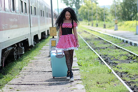 woman in red and white polka-dot dress holding teal luggage beside train during daytime