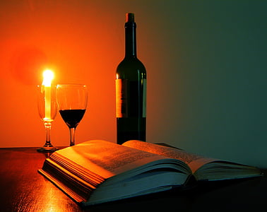 black glass bottle beside wine glasses filled with liquid and candle