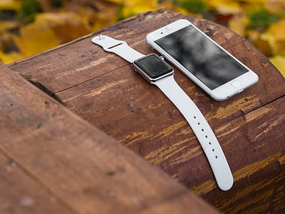 silver aluminum case Apple Watch with white Sport Band and silver iPhone 6 both on log