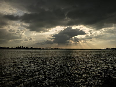 photo of island silhouette with clouds overhead