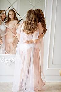 two women wearing white lace lingerie