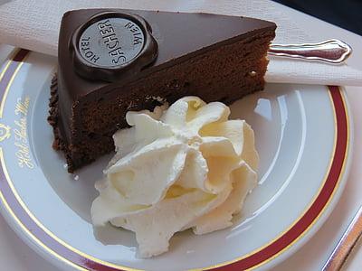 closeup photo of sliced chocolate cake with cream on ceramic plate