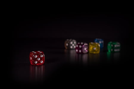 red die separated to multi-color dice in bokeh photography