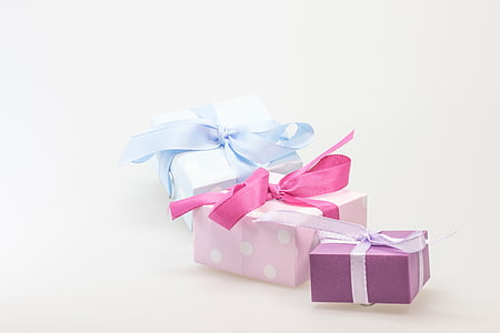 three pink, purple, and blue gift boxes on white background