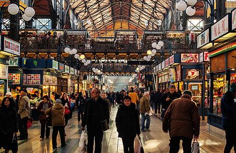 man wearing black jacket surround by stores