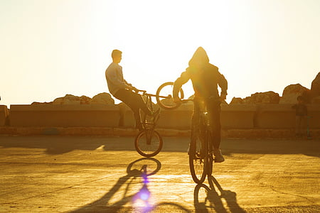 two person riding a bicycle doing tricks