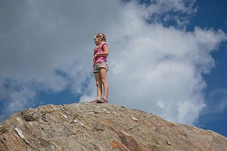 photo of girl standing on rock