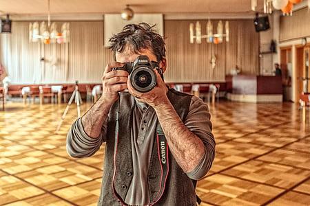 man taking photo using Canon bridge camera