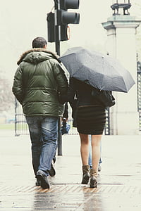 man in green park jacket walking beside woman in black dress with umbrella