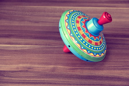 multicolored plastic spinning top toy on wooden surface