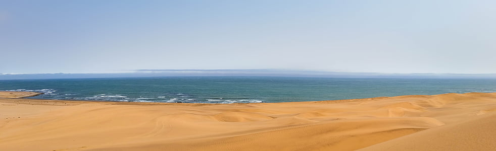 brown sand and body of water photography