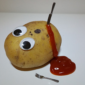 photography of knife on potato