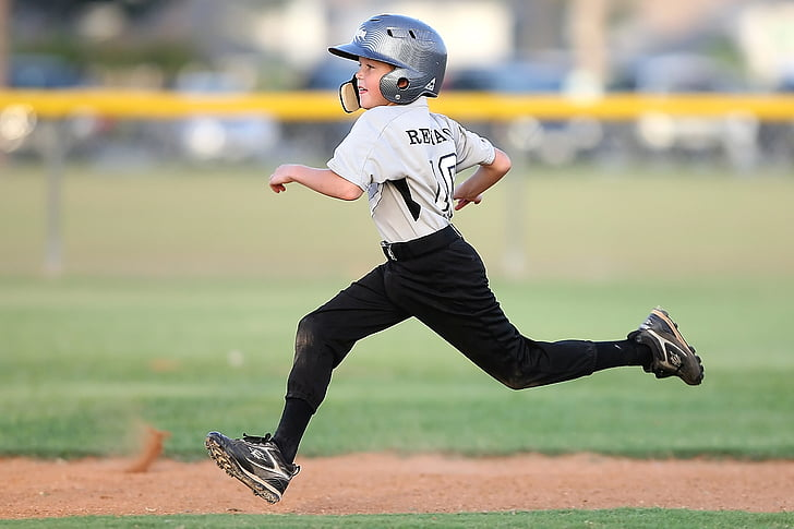 selective focus photography of boy wearing gray baseball shirt running on baseball field