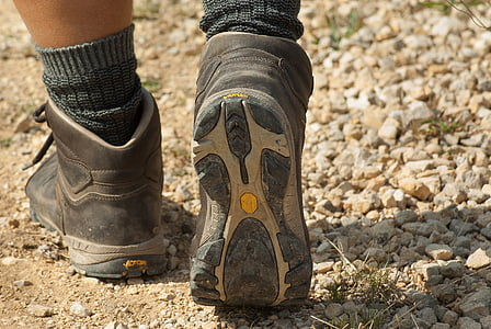 person wearing gray-and-white hiking boots