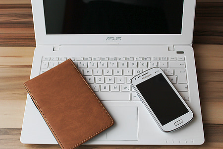 white ASUS laptop with Samsung Galaxy smartphone band brown leather case