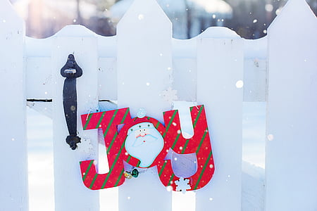 Joy signage on white wooden fence