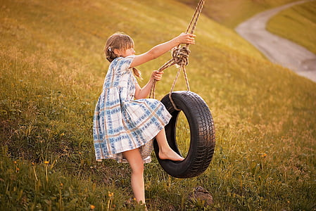 girl about to ride a swing vehicle tire at the green grass field