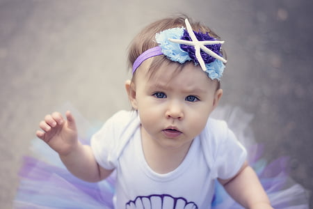 baby in white and purple tutu dress shallow focus photo