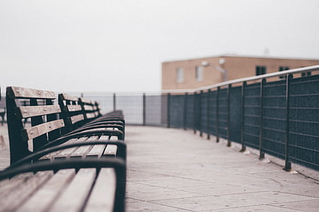 brown wooden bench near black metal fence on daytime