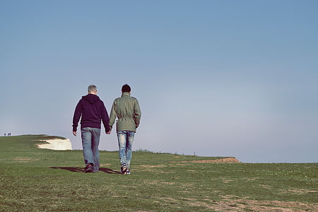 two person walking on green grass holding both hands during daytime