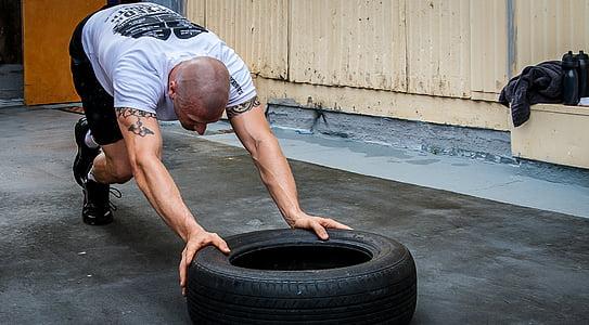 man pushing vehicle tire