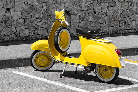 yellow motor scooter parked at side of street