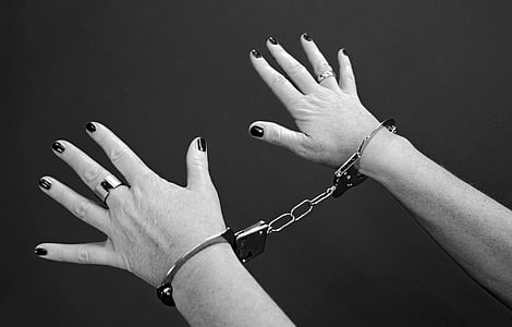 person showing hand with handcuffs