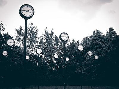 black analog clock post grayscale photo