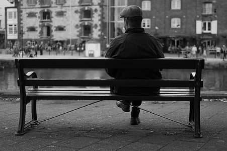 man sitting on bench front of building