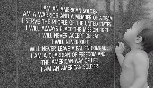 greyscale photo of topless toddler standing in front of I am an American soldier poem-printed wall