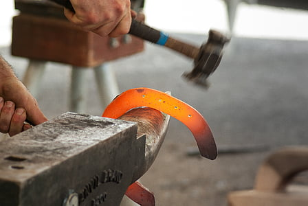 person holding glowing metal on anvil