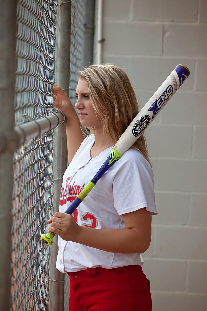woman in white St. Louis Cardinals jersey shirt holding baseball bat
