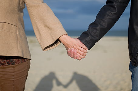 man and woman holding hands on seashore near beach