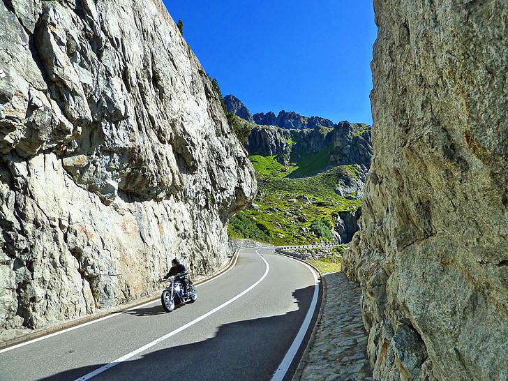 man riding on motorcycle driving along high-way during daytime