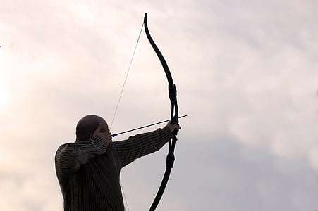 person wearing black long-sleeve top holding long bow