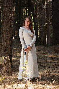 woman in grey scoop-neck long-sleeved dress holding sword while smiling