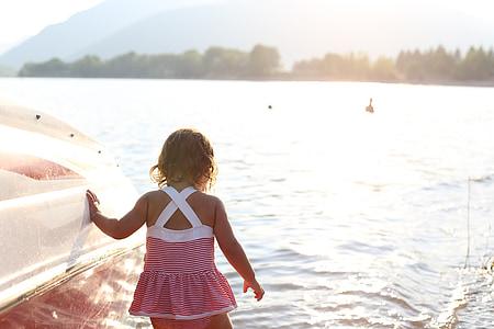 girl standing on water beside white boat