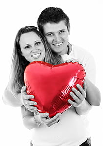 selective color photo of couple holding red heart balloon