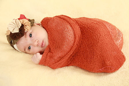 baby covered in red textile