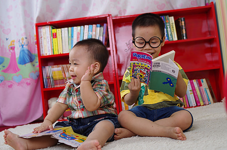 two boys reading books while sitting on floor