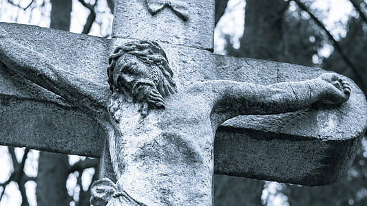 gray concrete crucifix near trees by day