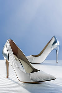 pair of silver leather pumps on white surface