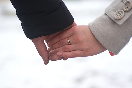 two persons holding hands during daytime