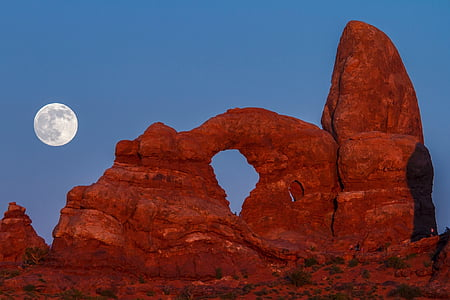 brown rock formation and moon photo