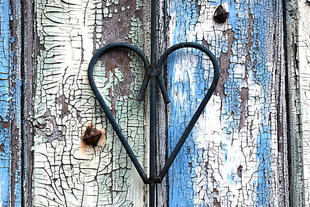 black wrought iron heart on white and blue wooden surface