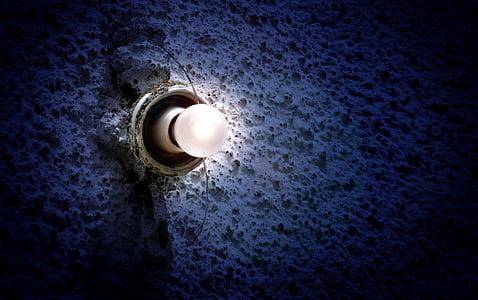white lightbulb on white concrete wall