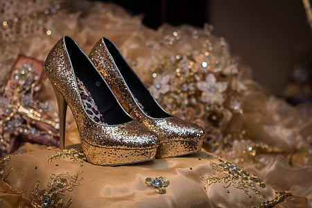 pair of gold glitter-type platform pumps on bed