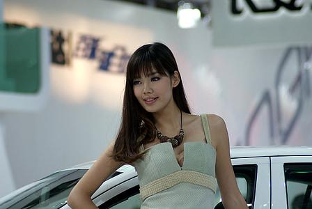 woman wearing white spaghetti strap top near white vehicle