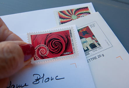 person holding red and white postage stamp