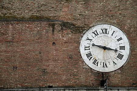 round white analog clock on wall at daytime
